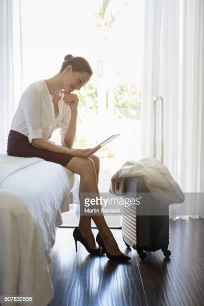 Businesswoman using digital tablet in hotel room