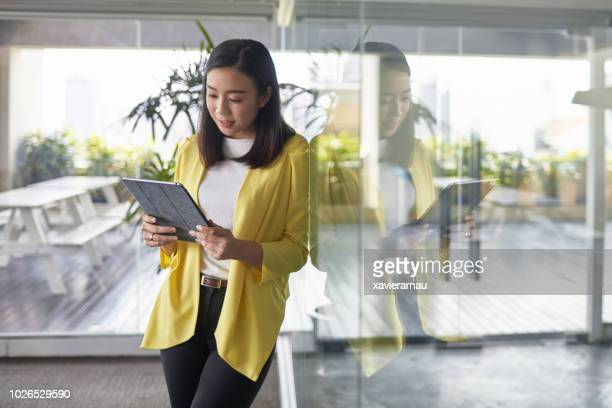 businesswoman using digital tablet in new office - smart casual stock pictures, royalty-free photos & images
