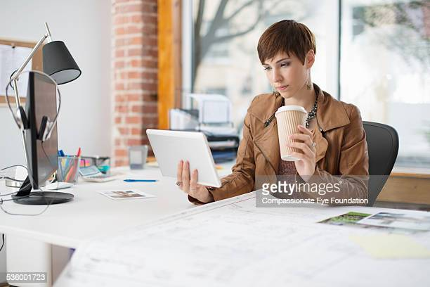 businesswoman using digital tablet in office - brown jacket stock pictures, royalty-free photos & images
