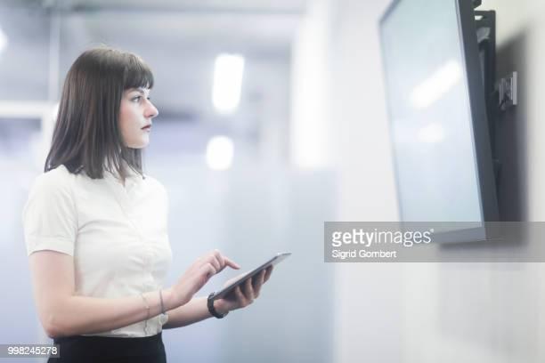 businesswoman using digital tablet looking at tv - sigrid gombert stock-fotos und bilder