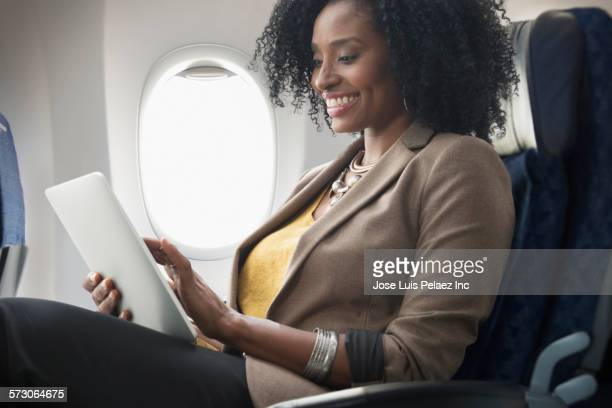 Businesswoman using digital tablet on airplane