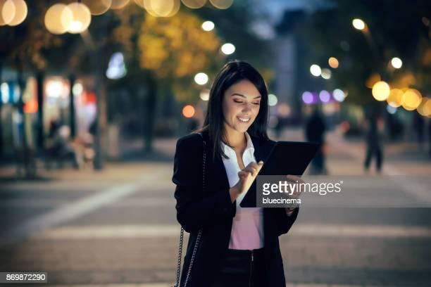 Geschäftsfrau mit digital-Tablette auf Straßen bei Nacht