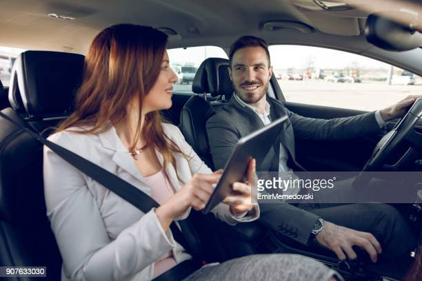 Businesswoman using digital tablet while businessman driving a car