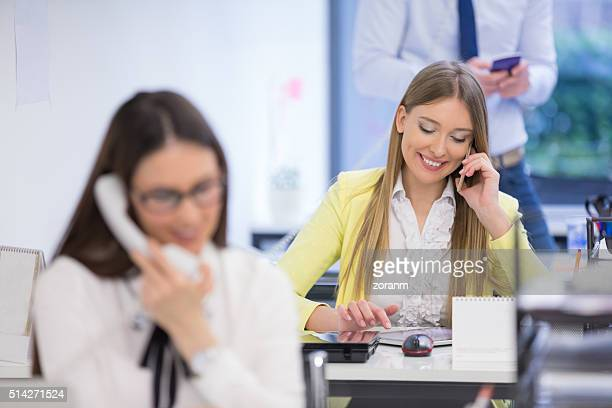 Businesswoman using digital tablet while talking the phone