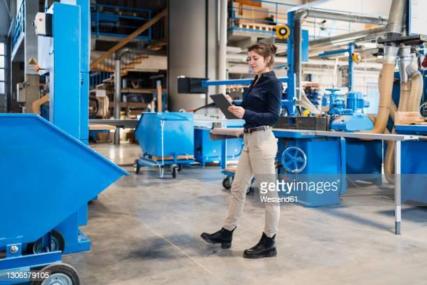 businesswoman using digital tablet while walking at industry - weibliche angestellte stock-fotos und bilder