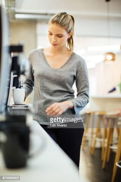 businesswoman using espresso maker at office - vネック ストックフォトと画像