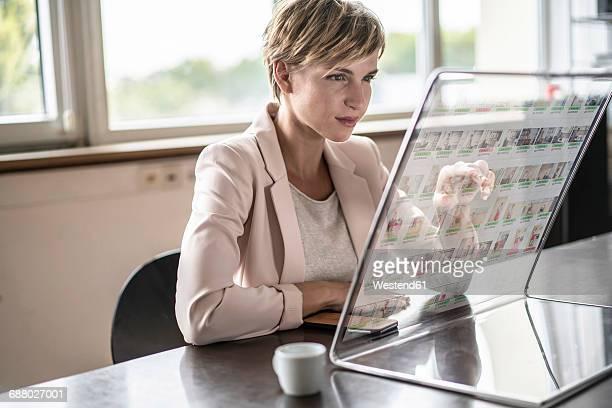 Businesswoman using futuristic modern computer in office