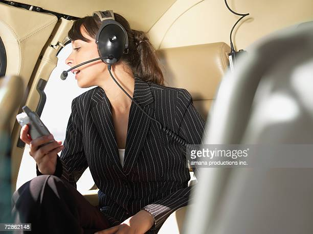 businesswoman using headset in helicopter - inside helicopter stock pictures, royalty-free photos & images