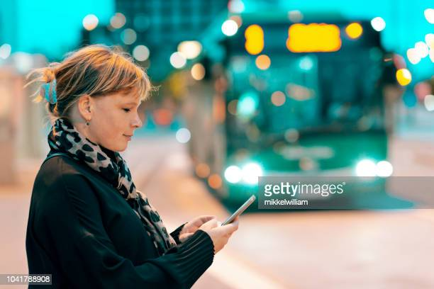 Businesswoman using her mobile phone on city street at night