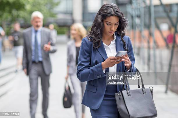 Businesswoman using her mobile phone while commuting in the city