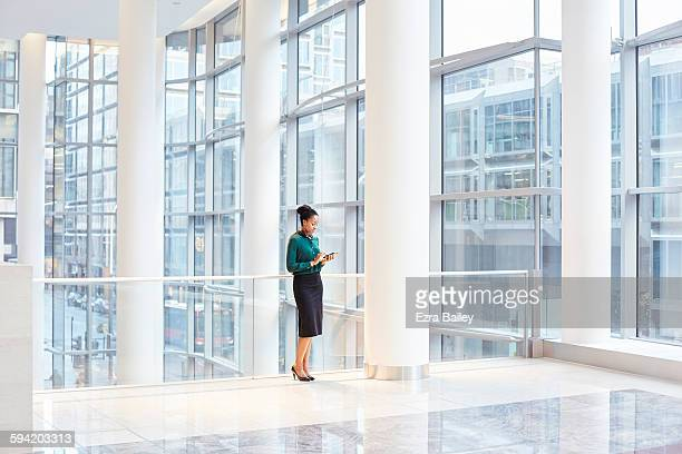 Businesswoman using her phone is smart office.