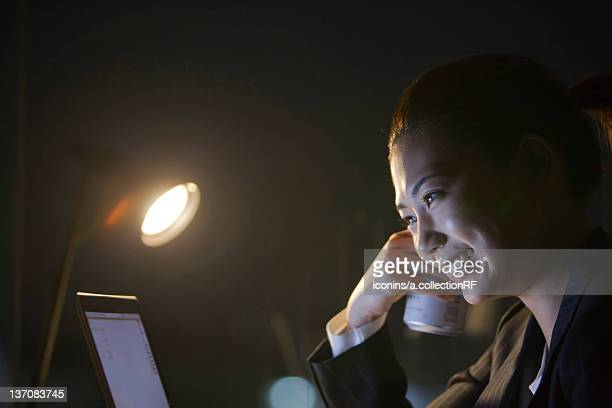 businesswoman using laptop and holding a can of beer in the dark, tokyo prefecture, honshu, japan - angle poise lamp stock pictures, royalty-free photos & images