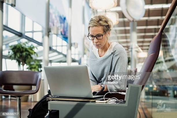 Businesswoman using laptop at airport lobby
