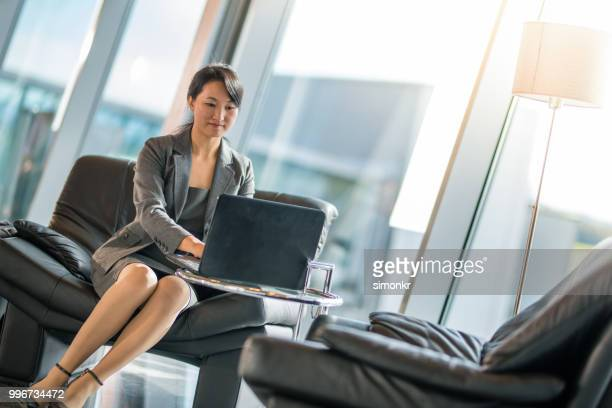 businesswoman using laptop at airport - gate stock pictures, royalty-free photos & images