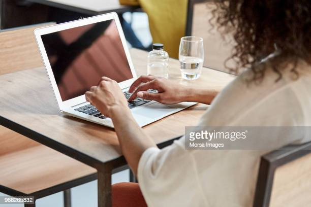 businesswoman using laptop at table in cafe - typen stockfoto's en -beelden