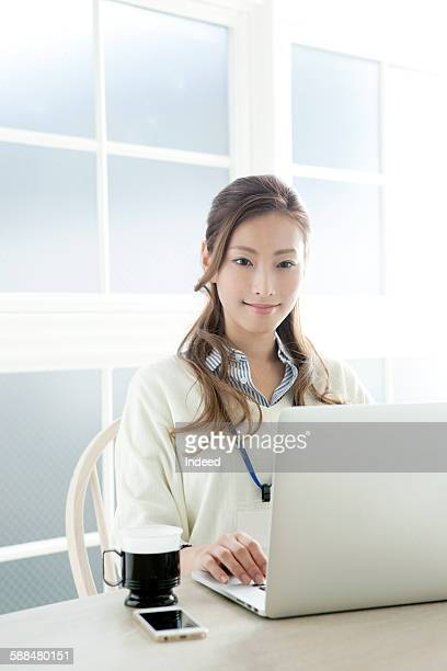 Businesswoman using laptop at table