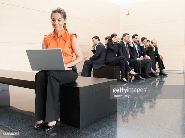 businesswoman using laptop away from co-workers - lingering stock pictures, royalty-free photos & images