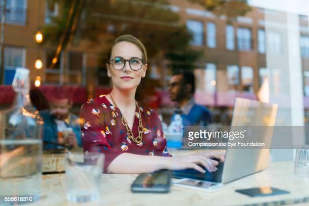 businesswoman using laptop in cafe - frau bluse durchsichtig stock-fotos und bilder