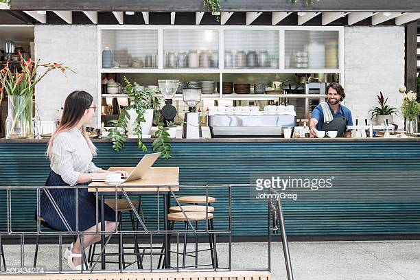 Businesswoman using laptop in cafe with waiter in background