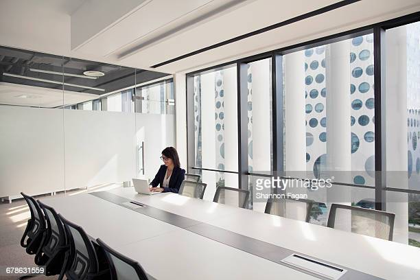businesswoman using laptop in conference room - middlebare afstand stockfoto's en -beelden