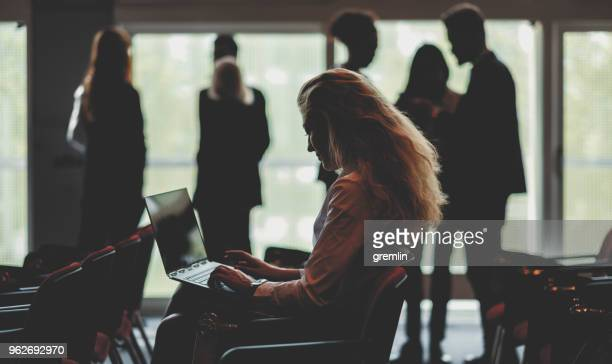 businesswoman using laptop in conference room - journalist stock pictures, royalty-free photos & images