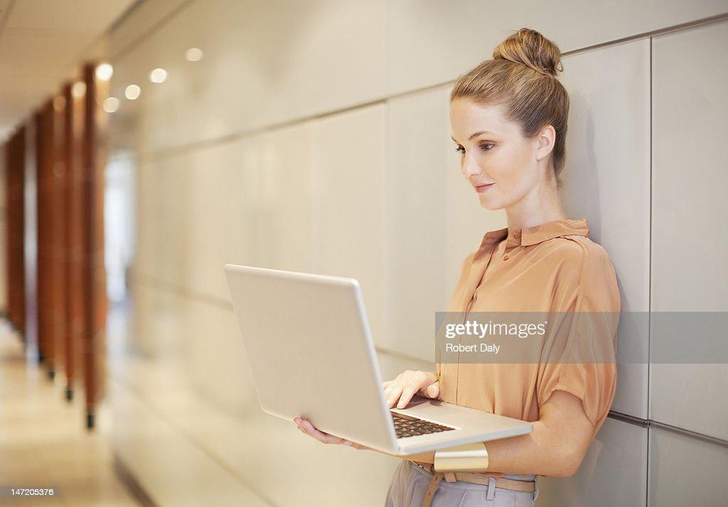 Businesswoman using laptop in corridor : Stock Photo