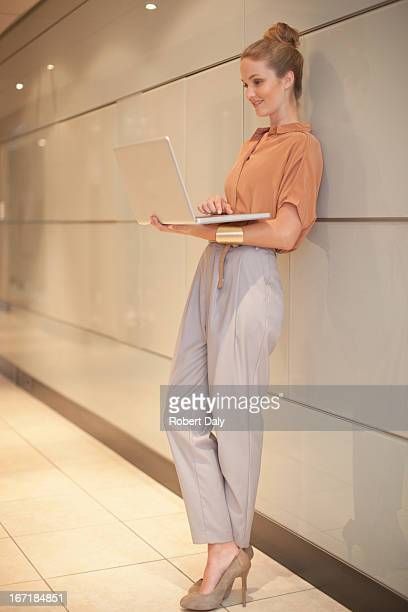 businesswoman using laptop in corridor - leaning stock pictures, royalty-free photos & images