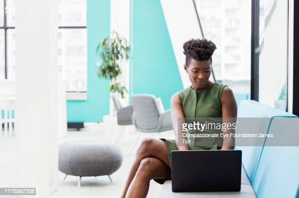 businesswoman using laptop in co-working space - compassionate eye foundation stock pictures, royalty-free photos & images