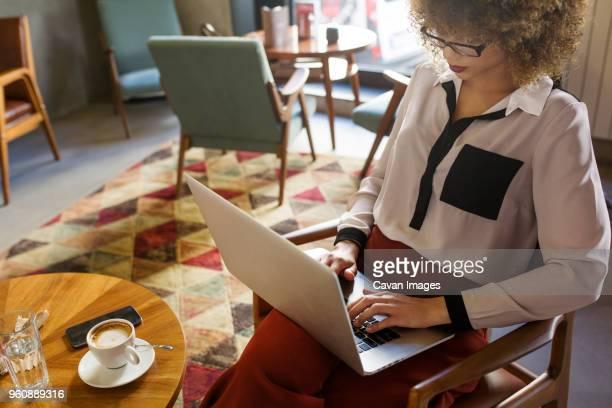 businesswoman using laptop in hotel lobby - trabalhadora de colarinho branco imagens e fotografias de stock