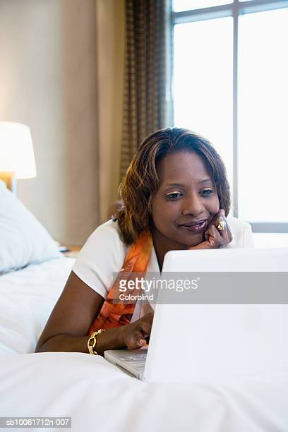 Businesswoman using laptop in hotel room, smiling