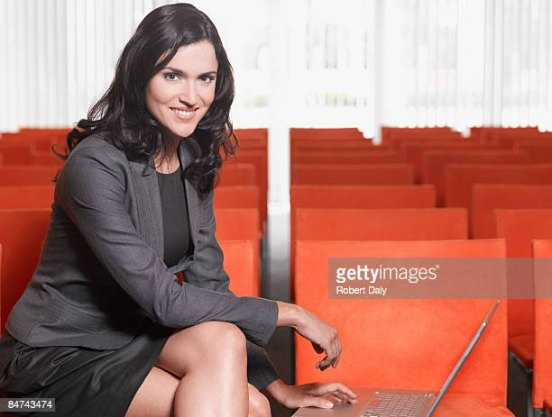 Businesswoman using laptop in lecture hall