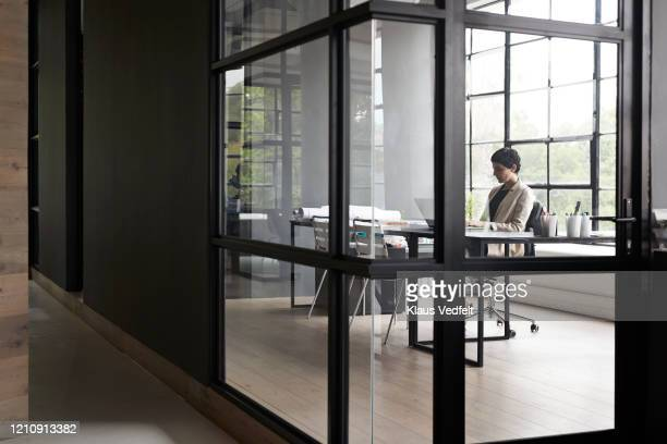 businesswoman using laptop in modern office - cream coloured blazer stock pictures, royalty-free photos & images