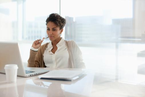 Businesswoman using laptop in office 167890561