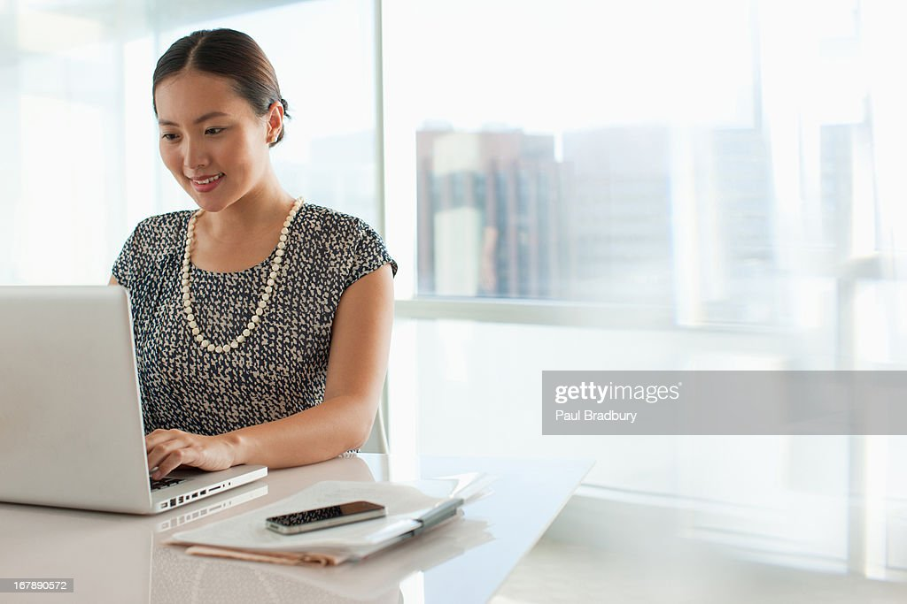 Businesswoman using laptop in office : Stock Photo
