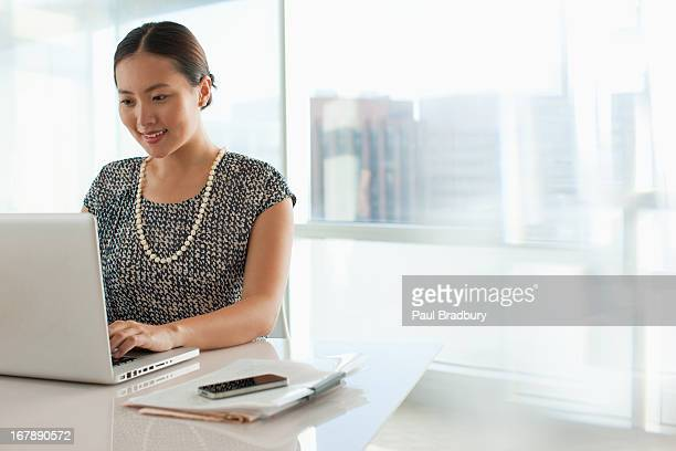 businesswoman using laptop in office - asian and indian ethnicities stock pictures, royalty-free photos & images