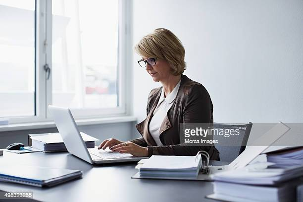businesswoman using laptop in office - behind stock pictures, royalty-free photos & images