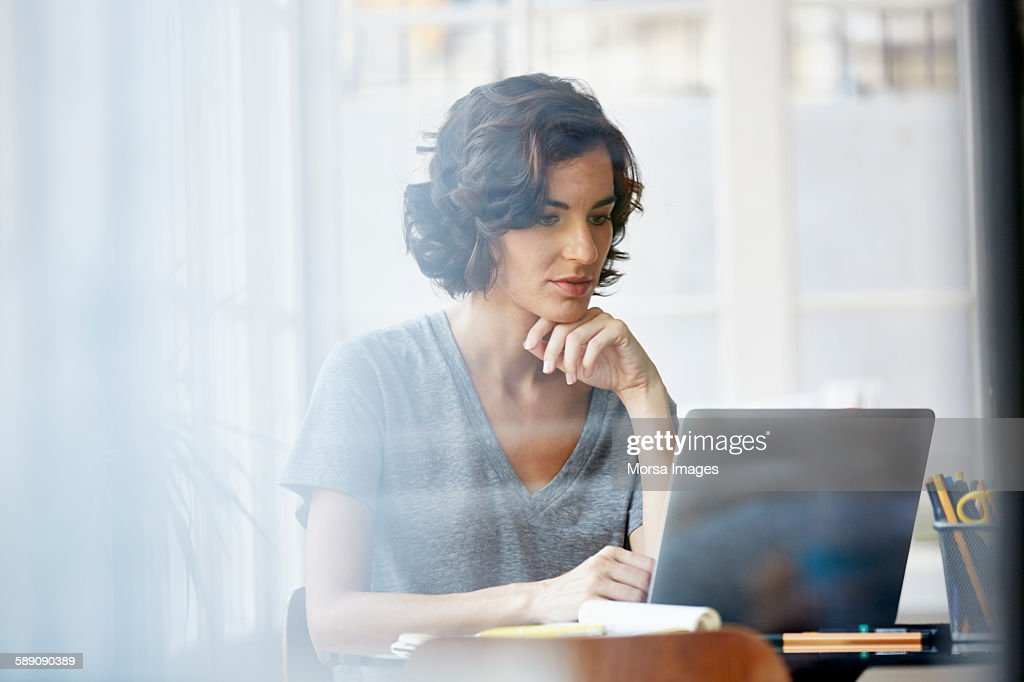 Businesswoman using laptop in office : Foto de stock