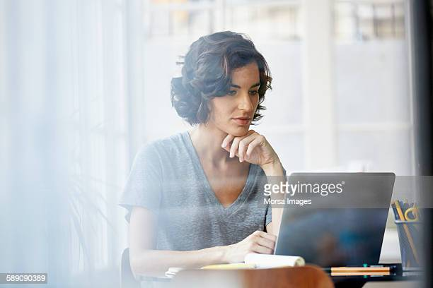 businesswoman using laptop in office - guardare in una direzione foto e immagini stock
