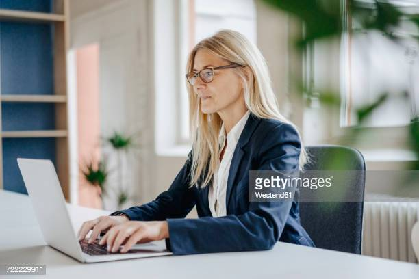 businesswoman using laptop in office - tippen stock-fotos und bilder