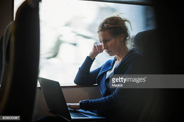 Businesswoman using laptop in train