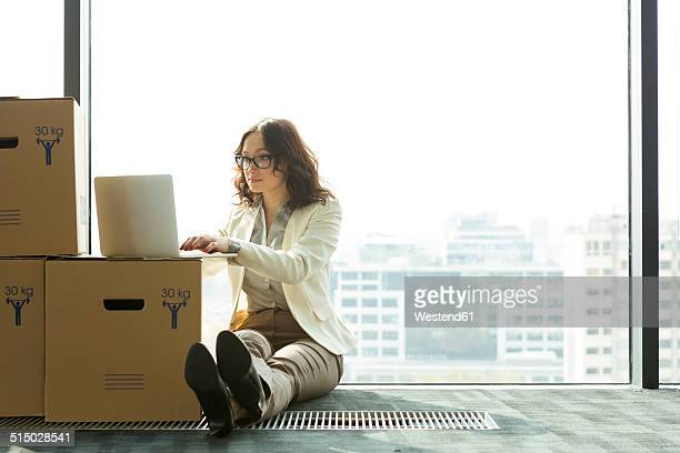 Businesswoman using laptop on empty office floor with cardboard boxes