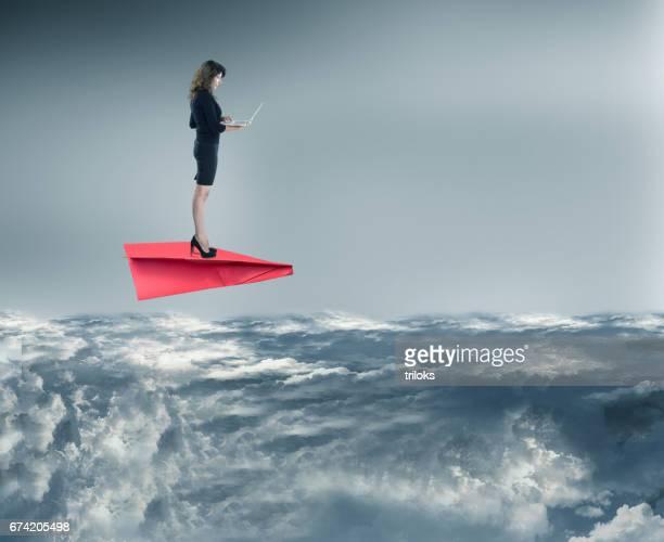 Geschäftsfrau mit Laptop auf Papierflugzeug während des Fluges über den Wolken