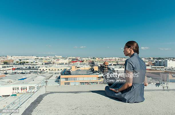 Businesswoman using laptop on roof terrace, Los Angeles, California, USA