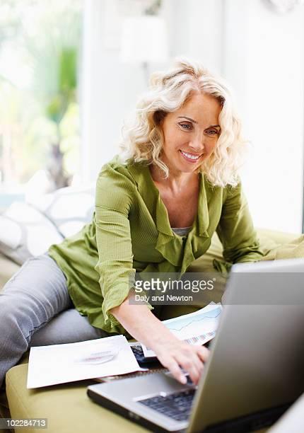Businesswoman using laptop on sofa