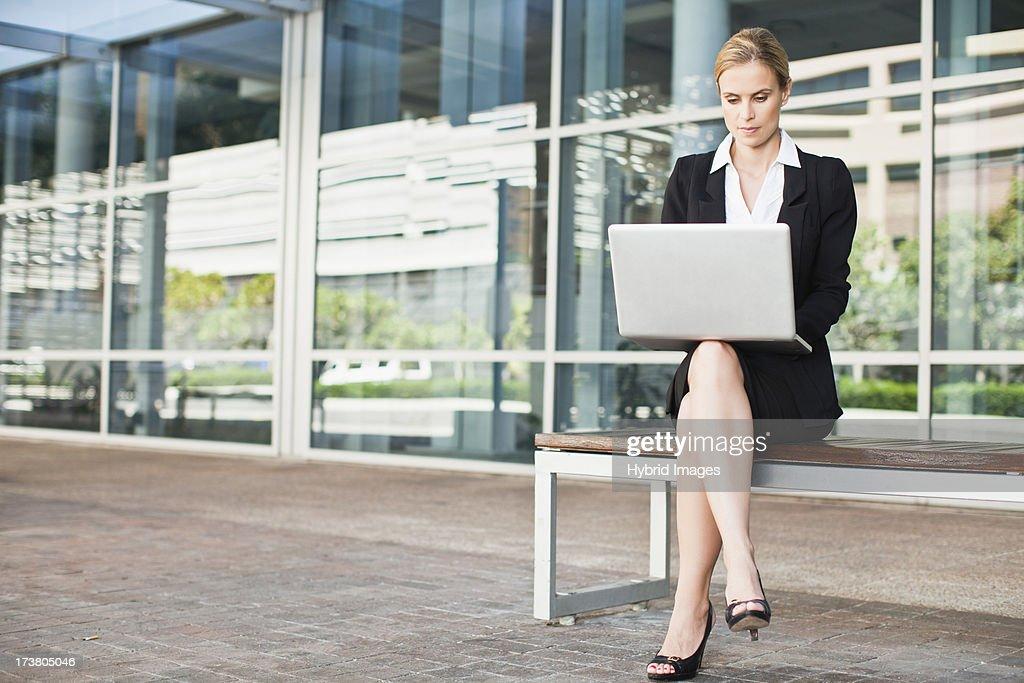 Businesswoman using laptop outdoors : Stock Photo