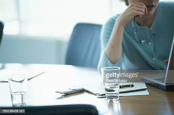 Businesswoman using laptop, part of