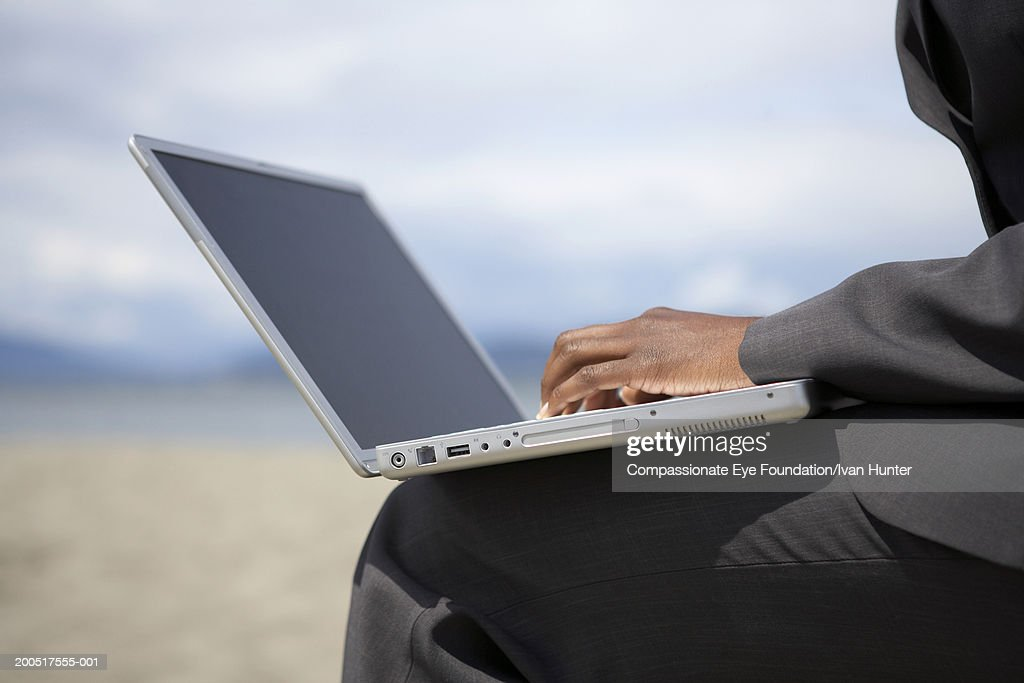 Businesswoman using laptop, side view, mid section : Stock Photo