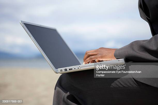 Businesswoman using laptop, side view, mid section