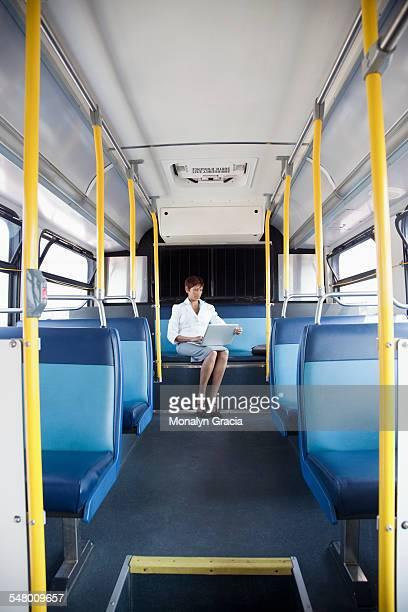 Businesswoman using laptop while riding public bus