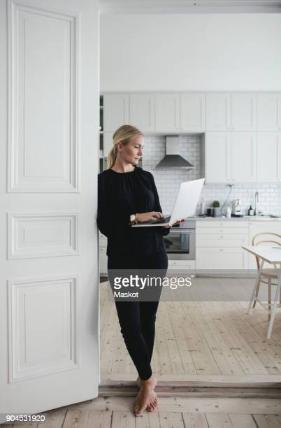 businesswoman using laptop while standing at doorway in home office - scandinavia stock pictures, royalty-free photos & images